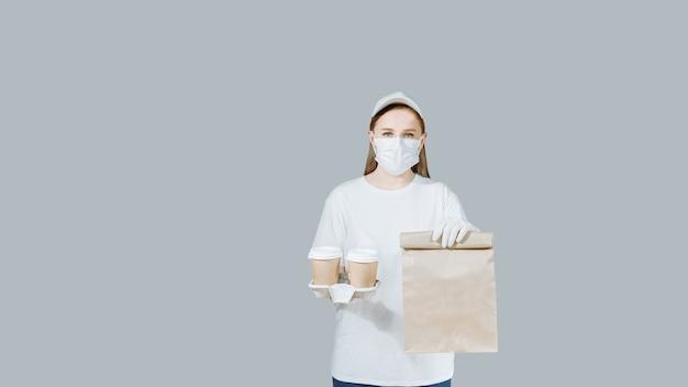 La ragazza del corriere in una maschera protettiva tiene un sacchetto di carta con il cibo e una tazza di caffè.