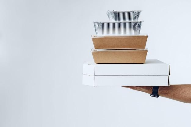 Mani del corriere che danno alto vicino imballato di consegna dell'alimento