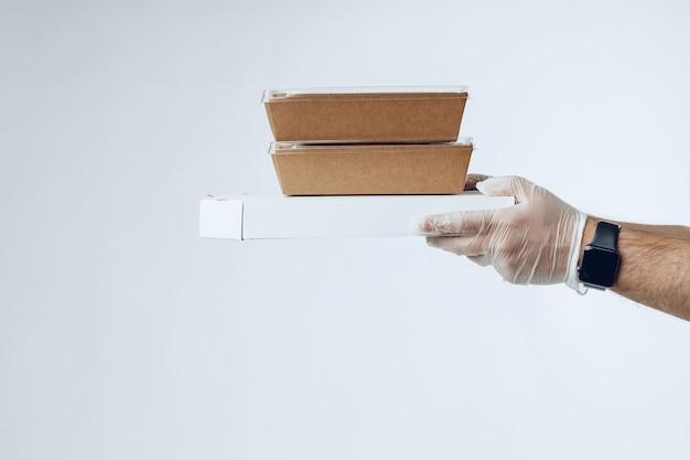 Mani del corriere in guanti di lattice che danno la consegna del cibo imballato