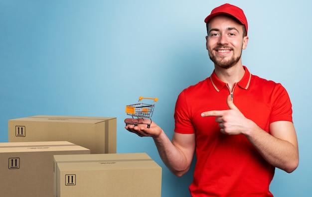 Courier ha in mano un piccolo carrello. concetto di negozio online. espressione emotiva. sfondo ciano