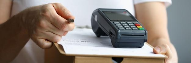 Il corriere tiene una scatola di cartone con terminale di pagamento e documenti con penna