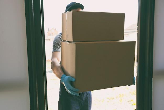 Il corriere consegna a casa una scatola di cartone con guanti in lattice e mascherina medica
