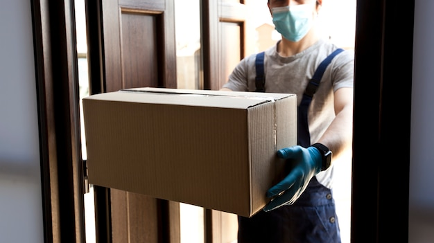 Il corriere consegna a casa la scatola di cartone con guanti in lattice e mascherina medica