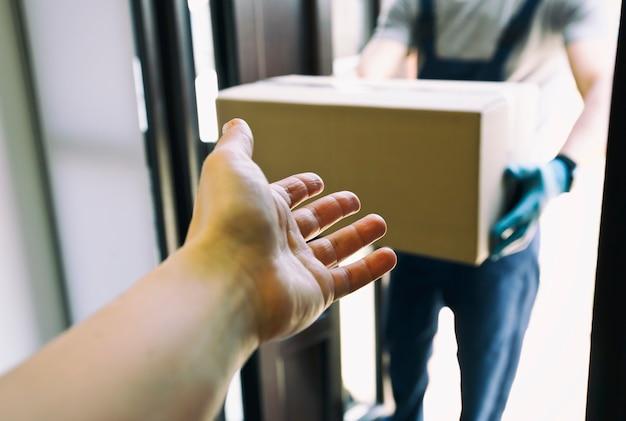 Il corriere sta consegnando la scatola di cartone a casa indossando guanti in lattice