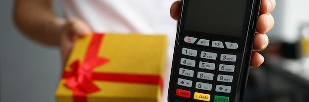 Il corriere tiene in mano una confezione regalo e un terminale di pagamento