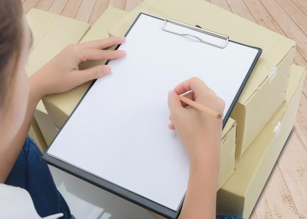 Corriere che fa le note nella ricevuta di consegna fra i pacchetti sulle scatole