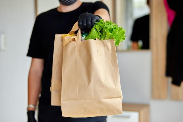 Uomo di corriere in scatola nera di consegna con cibo, consegna senza contatto.