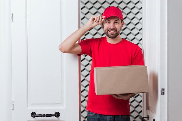 Uomo del corriere che tiene il suo cappuccio e una scatola