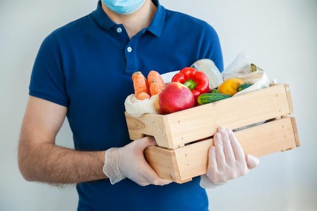 Uomo di corriere in guanti protettivi in possesso di una scatola piena di cibo