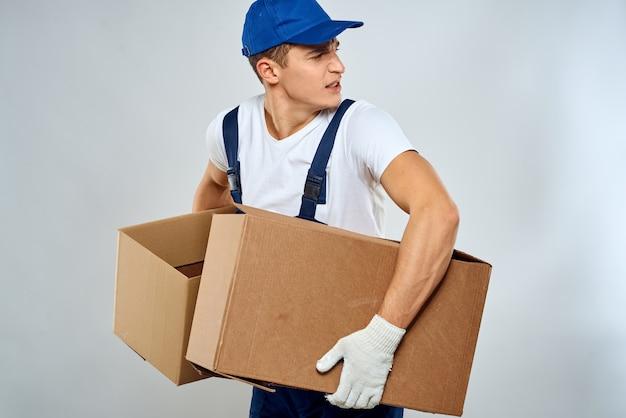 Uomo di corriere con scatola di cartone su grigio