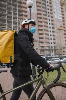 Corriere in mascherina medica che cammina con la sua bicicletta, guardandosi intorno in città