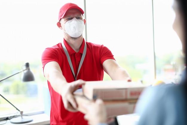 Corriere nella mascherina medica che trasporta il primo piano della pizza