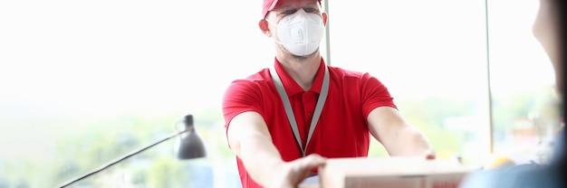 Corriere in maschera medica che consegna il primo piano della pizza
