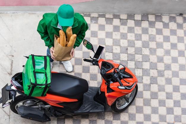 Il corriere vicino alla moto aspetta per consegnare il pane