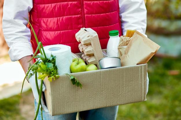 Il corriere in maschera protettiva e guanti medici consegna la scatola del cibo. cibo a domicilio durante l'epidemia di virus, panico da coronavirus e pandemie. rimanga sicuro. l'uomo tiene la scatola di donazione con il cibo.