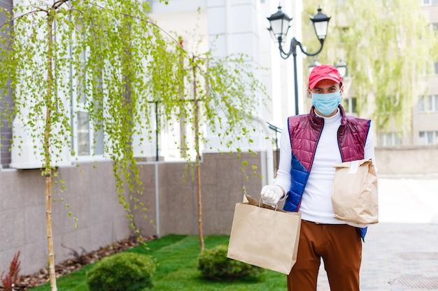 Il corriere in maschera protettiva e guanti medici consegna cibo da asporto. servizio di consegna in quarantena, focolaio di malattia, condizioni di pandemia di coronavirus covid-19.