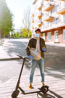 Il corriere in maschera protettiva e guanti medici su uno scooter consegna pacchi di carta artigianale con cibo. servizio di consegna in quarantena, epidemia di malattia, condizioni pandemiche di coronavirus covid-19.