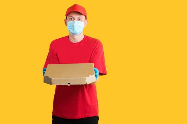 Il corriere in uniforme rossa tiene una scatola in una maschera e guanti su colore giallo