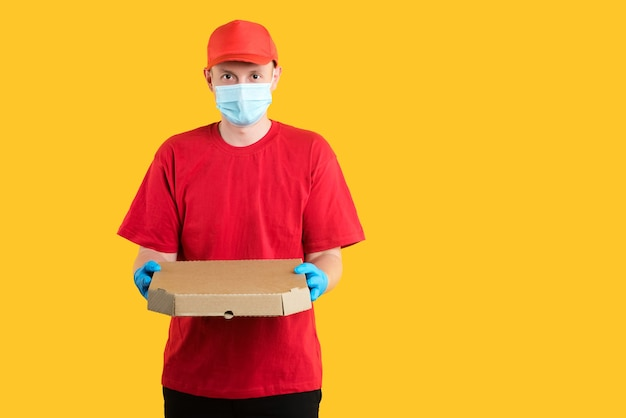 Corriere in uniforme rossa che indossa maschera e guanti su colore giallo