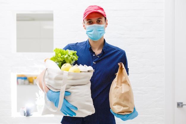 Le mani del corriere in guanti medici bianchi in lattice consegnano pacchi in confezioni alimentari alla porta durante l'epidemia di coronovirus, covid-19. consegna sicura degli ordini online durante l'epidemia.