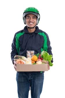 Corriere indossa casco e giacca uniforme tenendo il cibo isolato su sfondo bianco