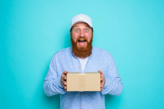 Il corriere con la scatola di cartone in mano è sorpreso di qualcosa