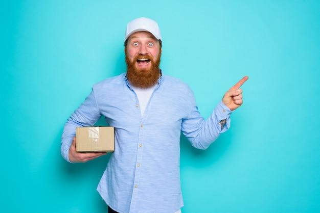 Il corriere con la scatola di cartone in mano è sorpreso e indica qualcosa