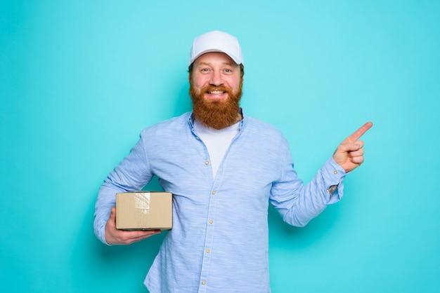 Il corriere con cappello è felice di consegnare una scatola di cartone e indica qualcosa