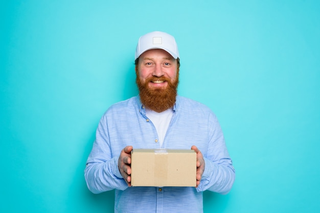 Il corriere con cappello è felice di consegnare una scatola di cartone