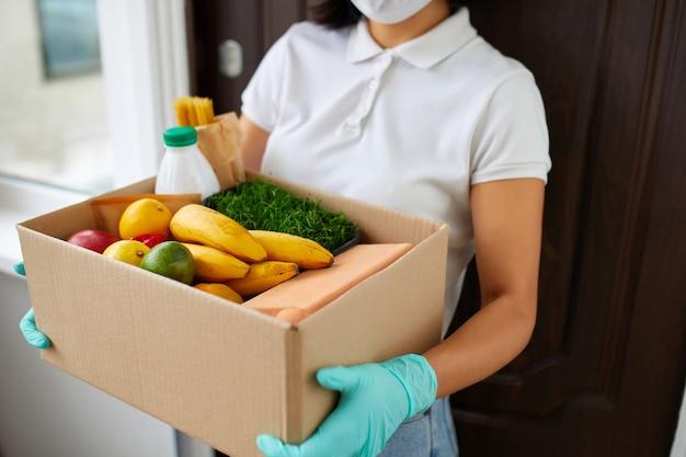 Corriere con scatola di imballaggio con cibo, consegna senza contatto, servizio di quarantena di coronavirus pandemico, donna volontaria con maschera protettiva bianca e scatola di donazione consegna guanti a casa.