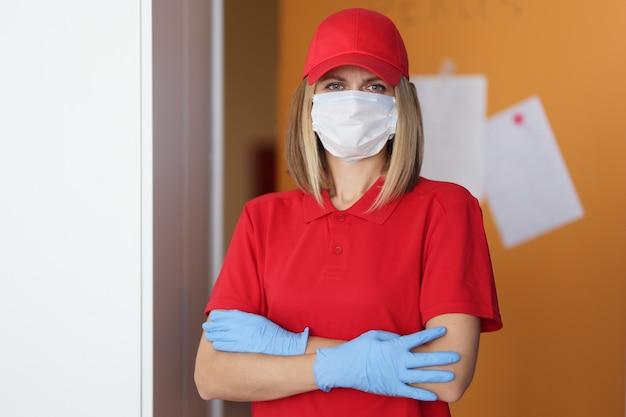Donna del corriere in maschera protettiva medica e guanti protettivi