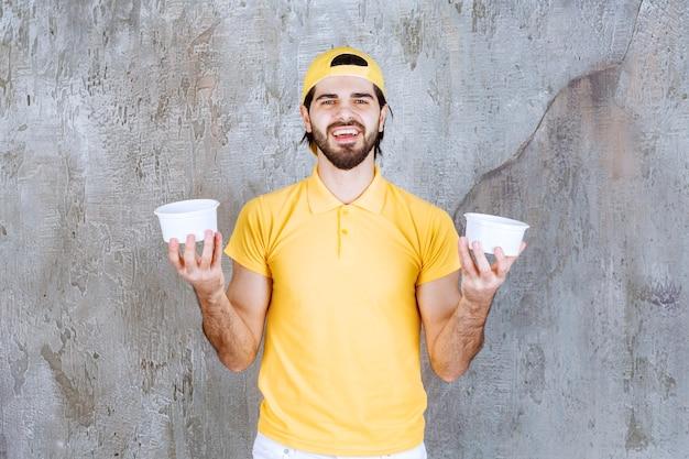 Corriere in uniforme gialla che tiene un bicchiere di plastica
