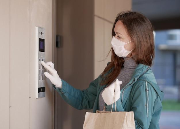 Le mani dei corrieri in guanti medicali consegnano pacchi di ordini online durante l'epidemia