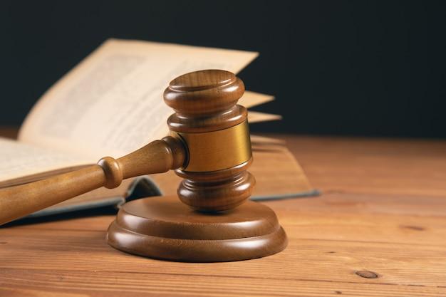 Martelletto e libro della corte sulla tavola di legno