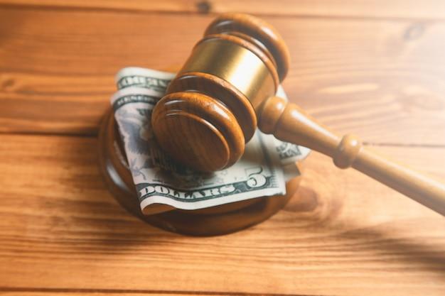 Martelletto di corte con soldi su un tavolo di legno