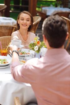 Uomo cortese. il cortese uomo dai capelli scuri si sente benissimo mentre dà una tazza di gustoso tè caldo alla sua ragazza