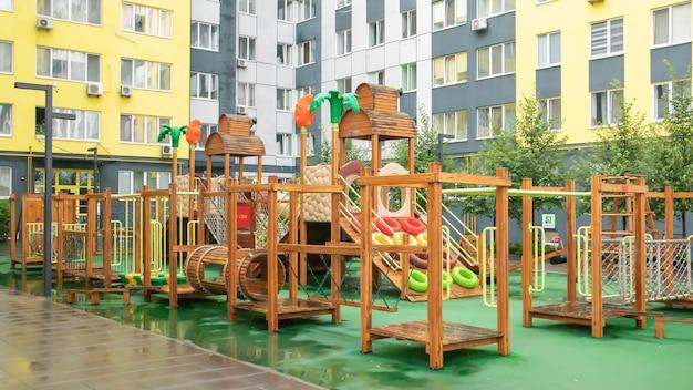 Un cortile di grattacieli con un moderno e grande parco giochi in legno e plastica in una piovosa giornata estiva senza persone. parco giochi all'aperto vuoto. un luogo per i giochi e gli sport dei bambini.