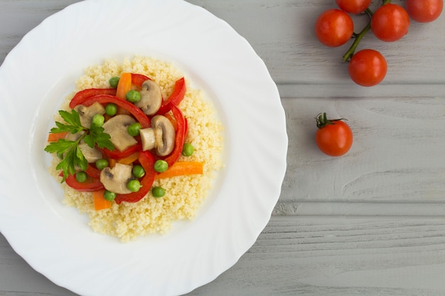 Cuscus con le verdure nel piatto bianco sul tavolo di legno grigio. vista dall'alto. copia spazio. avvicinamento.
