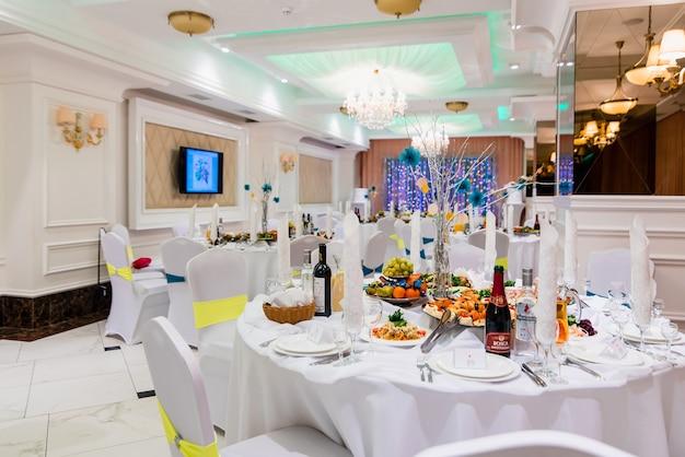 Tavolo da pranzo coperto in una lussuosa sala banchetti bianca brillante per eventi di nozze