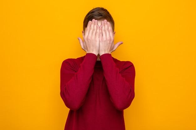 Faccia coperta di mani giovane bel ragazzo che indossa un maglione rosso