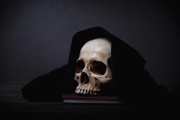 Teschio umano coperto posato su una scrivania