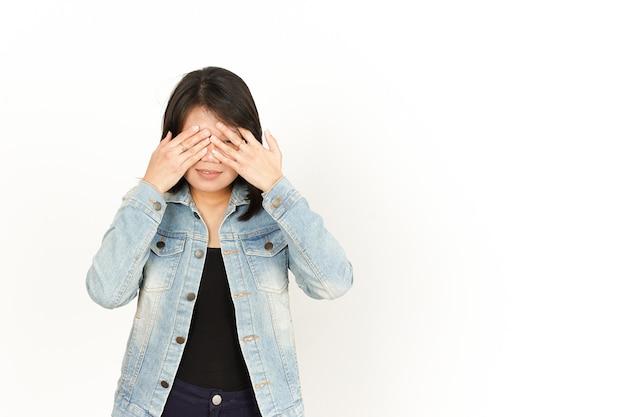 Coprendo gli occhi di bella donna asiatica che indossa giacca di jeans e camicia nera isolata su white