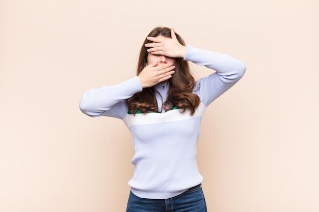 Coprendo il viso con entrambe le mani dicendo no alla telecamera! rifiutare foto o proibire foto