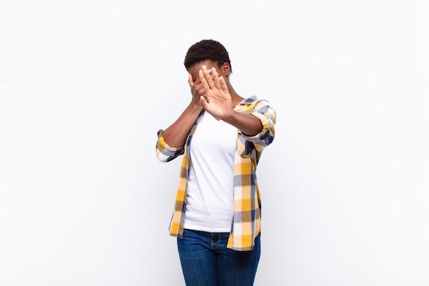 Coprendo il viso con la mano e mettendo l'altra mano in avanti per fermarsi, rifiutando foto o immagini