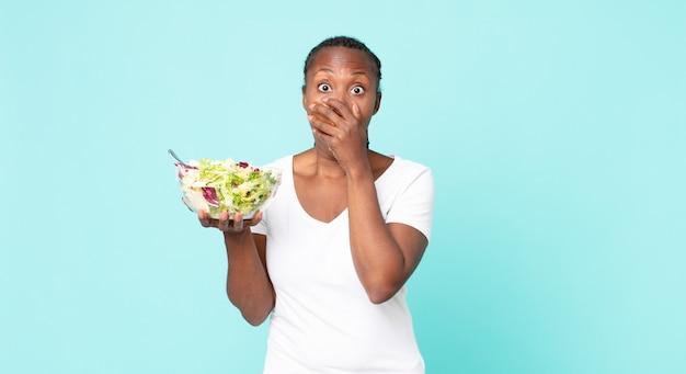 Coprendo la bocca con le mani con uno shock e tenendo in mano un'insalata