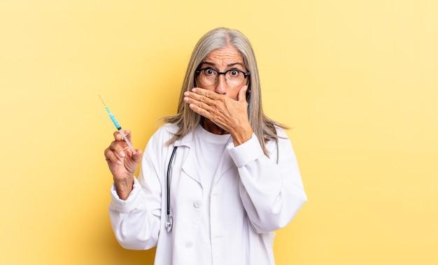 Coprirsi la bocca con le mani con un'espressione scioccata e sorpresa, mantenere un segreto o dire oops. medico e concetto di vaccino
