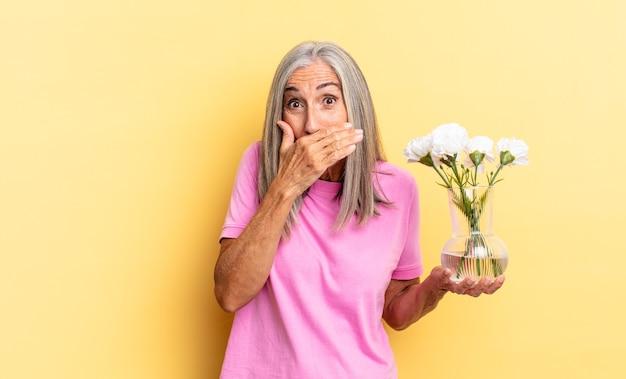 Coprirsi la bocca con le mani con un'espressione scioccata e sorpresa, mantenere un segreto o dire oops tenendo fiori decorativi