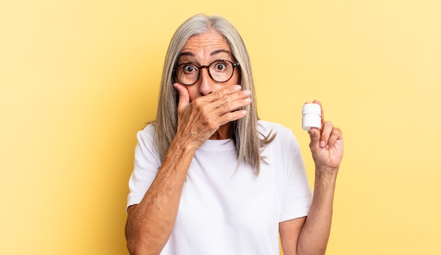 Coprirsi la bocca con le mani con un'espressione scioccata e sorpresa, mantenere un segreto o dire oops e tenere in mano un flacone di pillole