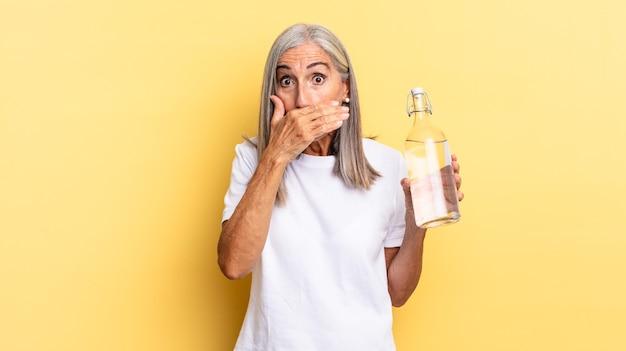 Coprirsi la bocca con le mani con un'espressione scioccata e sorpresa, mantenere un segreto o dire oops e tenere in mano una bottiglia d'acqua