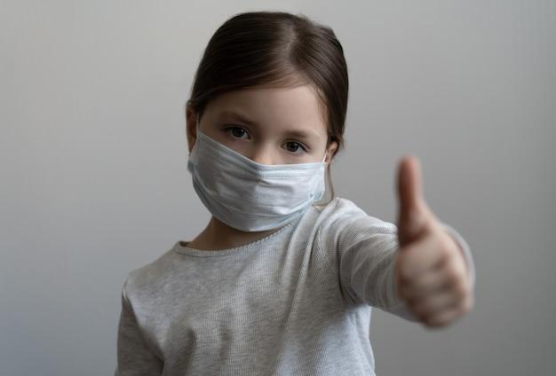 Covid-19 e concetto di inquinamento atmosferico. bambina che indossa la maschera per proteggere e pollice in alto gesto per fermare lo scoppio del virus corona coronavirus e sintomi del virus epidemico